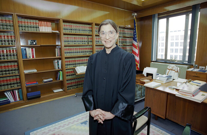FILE- In this Aug. 3, 1993, file photo, then-Judge Ruth Bader Ginsburg poses in her robe in her office at U.S. District Court in Washington. Earlier, the Senate voted 96-3 to confirm Bader as the 107th justice and the second woman to serve on the Supreme Court. Ruth Bader Ginsburg died at her home in Washington, on Sept. 18, 2020, the Supreme Court announced. (AP Photo/Doug Mills, File)