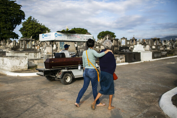 Relatives accompany the coffin that contains the remains of 89-year-old Irodina Pinto Ribeiro, who died from COVID-19 related complications, at the Inhauma cemetery in Rio de Janeiro, Brazil, Friday, June 18, 2021. Brazil is approaching an official COVID-19 death toll of 500,000 — second-highest in the world. (AP Photo/Bruna Prado)