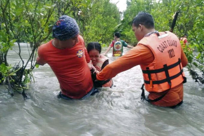 In this photo provided by the Philippine Coast Guard, residents wade along floodwaters as they are evacuated to safer grounds in Naujan, Oriental Mindoro province, central Philippines on Friday July 23, 2021. Thousands of residents fled from flooded communities and swollen rivers in the Philippine capital and outlying provinces Saturday after days of torrential monsoon rains, which left at least one villager dead, officials said. (Philippine Coast Guard via AP)