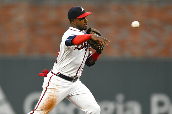 FILE - In this Sept. 21, 2019, file photo, Atlanta Braves second baseman Adeiny Hechavarria throws out San Francisco Giants' Evan Longoria at first base after forcing out Buster Posey at second for a double play during the first inning of a baseball game in Atlanta. The Braves have boosted their infield depth by re-signing Hechavarria to a $1 million, one-year deal. (AP Photo/John Amis, File)
