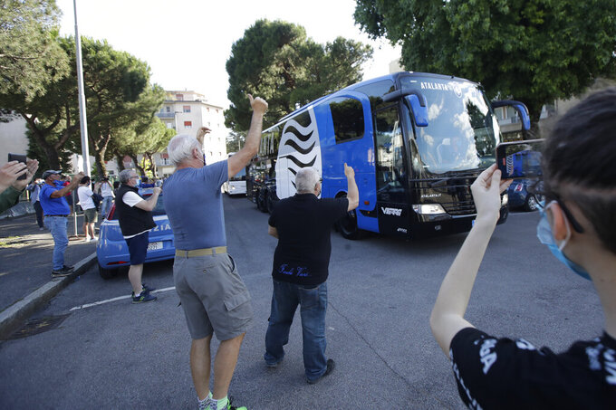 Fans wave as the coach of Atalanta team arrives, prior to the Serie A soccer match between Atalanta and Sassuolo at the Gewiss Stadium in Bergamo, Italy, Sunday, June 21, 2020. This is the first game to be played in Bergamo since easing of lockdown measures, in the area that has been the epicenter of the hardest-hit province of Italy's hardest-hit region, Lombardy, the site of hundreds of COVID-19 deaths. (AP Photo/Luca Bruno)