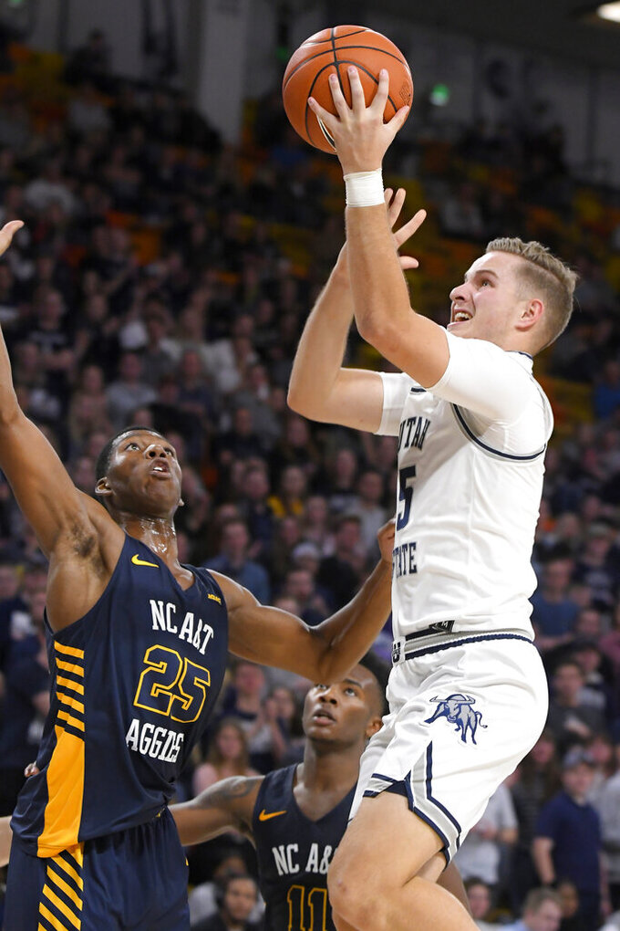 Utah State guard Sam Merrill (5) shoots as North Carolina A&T forward Webster Filmore (25) and guard Tyler Maye defend during the first half of an NCAA college basketball game Friday, Nov. 15, 2019, in Logan, Utah. (AP Photo/Eli Lucero)