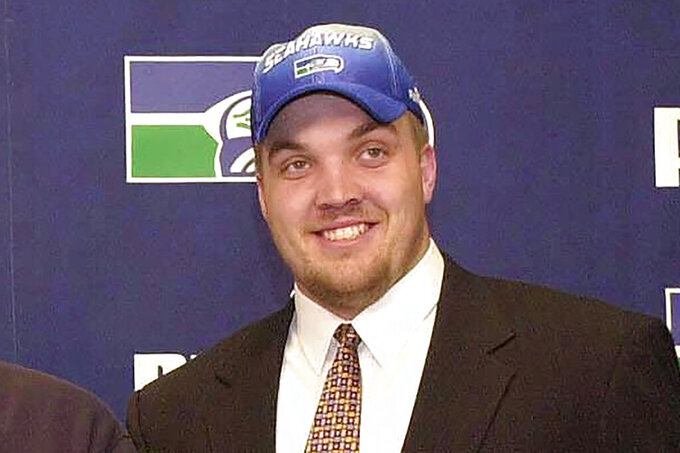 FILE - Chris McIntosh smiles as the Seattle Seahawks first-round draft pick is shown during an introductory press conference in Kirkland, Washington, in this April 16, 2000, file photo. Chris McIntosh played for Barry Alvarez on two of Wisconsin's Rose Bowl championship teams and spent the last few years working as his right-hand man. Now he is about to succeed his former coach and boss as the Badgers' athletic director. Chancellor Rebecca Blank announced Wednesday, June 2, 2021, that McIntosh will take over when Alvarez finalizes his retirement. (AP Photo/Jay Drowns, File)