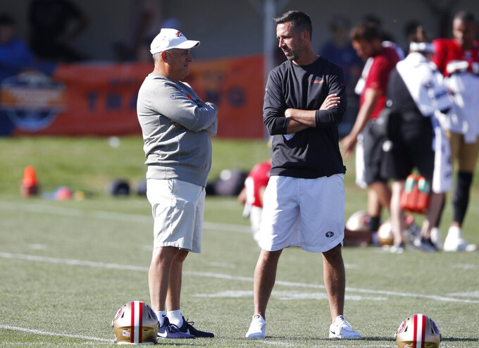 Denver Broncos head coach Vic Fangio, left, chats with San Francisco 49ers head coach Kyle Shanahan during a combined NFL training camp Saturday, Aug. 17, 2019, at the Broncos' headquarters in Englewood, Colo. (AP Photo/David Zalubowski)