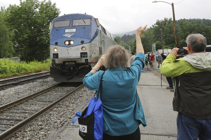 An onlooker waves as the Amtrak Vermonter passenger train arrives at the Montpelier station, in Berlin, Vt., on Monday July 19, 2021. A celebration was held at Amtrak stations across Vermont to mark the return of the passenger trains to Vermont for the first time since they were suspended at the beginning of the COVID-19 pandemic. (AP Photo/Wilson Ring)