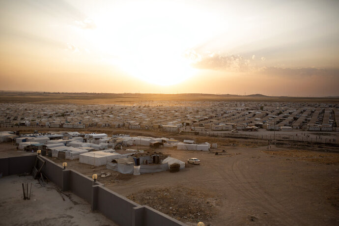 In this Aug. 24, 2019 photo, the sun sets over Sharia Camp, where Yazidis displaced by Islamic State militants are housed near Dohuk, Iraq. Some 3,500 Yazidi slaves have been freed from IS' clutches in recent years, most of them ransomed by their families. But more than 2,900 Yazidis remain unaccounted for, including some 1,300 women and children, according to the Yazidi abductees office in Iraq's Kurdish autonomous region. (AP Photo/Maya Alleruzzo)