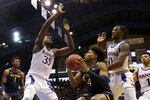 West Virginia's Miles McBride (4) looks to shoot under pressure from Kansas' Udoka Azubuike (35) and Marcus Garrett (0) during the second half of an NCAA college basketball game Saturday, Jan. 4, 2020, in Lawrence, Kan. (AP Photo/Charlie Riedel)