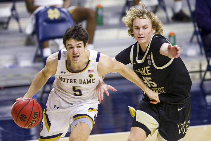 Notre Dame's Cormac Ryan (5) drives in next to Wake Forest's Carter Whitt (35) during the second half of an NCAA college basketball game Tuesday, Feb. 2, 2021, in South Bend, Ind. Notre Dame won 79-58. (AP Photo/Robert Franklin)