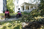 Ella Shears, left, and Mary Walker watch workers remove branches on a power line in their neighborhood, Friday, Aug. 14, 2020, in Cedar Rapids, Iowa. The storm that struck Monday morning left tens of thousands of Iowans without power as of Friday morning. (AP Photo/Charlie Neibergall)