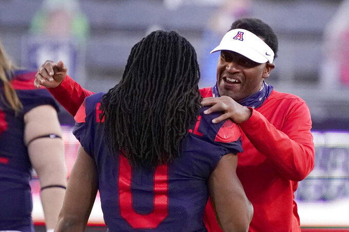 In this Friday, Dec. 11, 2020, photo, Arizona coach Kevin Sumlin talks to a player as the team's NCAA college football game against Arizona State in Tucson, Ariz. Arizona fired Sumlin on Saturday, Dec. 12, a day after a 70-7 loss to Arizona State extended the Wildcats' losing streak to a record 12 games over two seasons.(AP Photo/Rick Scuteri)