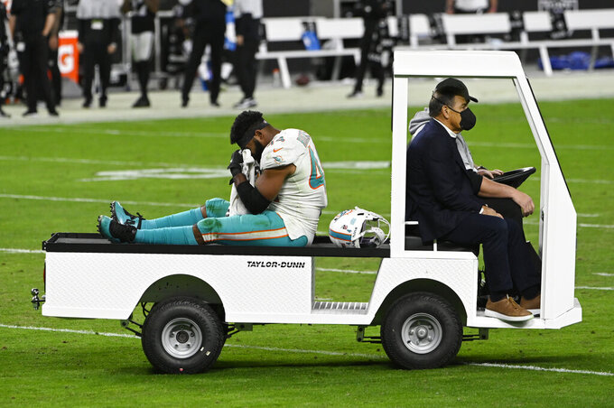 Miami Dolphins outside linebacker Elandon Roberts (44) is driven off the field after an injury against the Las Vegas Raiders during the second half of an NFL football game, Saturday, Dec. 26, 2020, in Las Vegas. (AP Photo/David Becker)