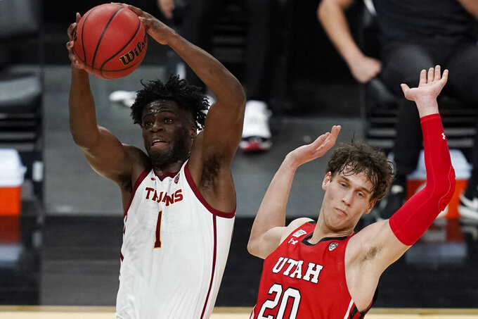 Southern California's Chevez Goodwin (1) grabs a rebound over Utah's Mikael Jantunen (20) during the first half of an NCAA college basketball game in the quarterfinal round of the Pac-12 men's tournament Thursday, March 11, 2021, in Las Vegas. (AP Photo/John Locher)