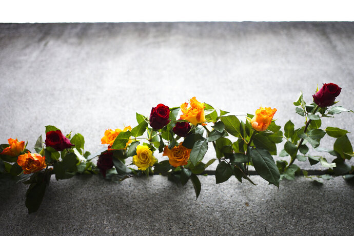 Flowers stuck in remains of the Berlin Wall during a commemoration ceremony to celebrate the 30th anniversary of the fall of the Berlin Wall at the Wall memorial site at Bernauer Strasse in Berlin, Saturday, Nov. 9, 2019. (AP Photo/Markus Schreiber)