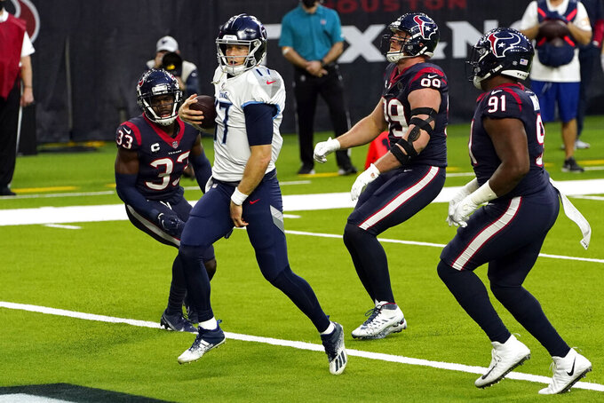 Tennessee Titans quarterback Ryan Tannehill (17) runs for a touchdown as Houston Texans' A.J. Moore Jr. (33), J.J. Watt (99) and Carlos Watkins (91) defend during the second half of an NFL football game Sunday, Jan. 3, 2021, in Houston. (AP Photo/Sam Craft)