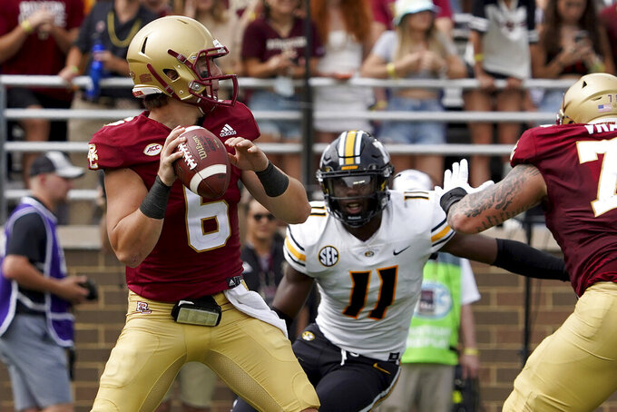 Boston College quarterback Dennis Grosel (6) drops back to pass as Missouri linebacker Devin Nicholson (11) pursues him during the first half of an NCAA college football game, Saturday, Sept. 25, 2021, in Boston. (AP Photo/Mary Schwalm)