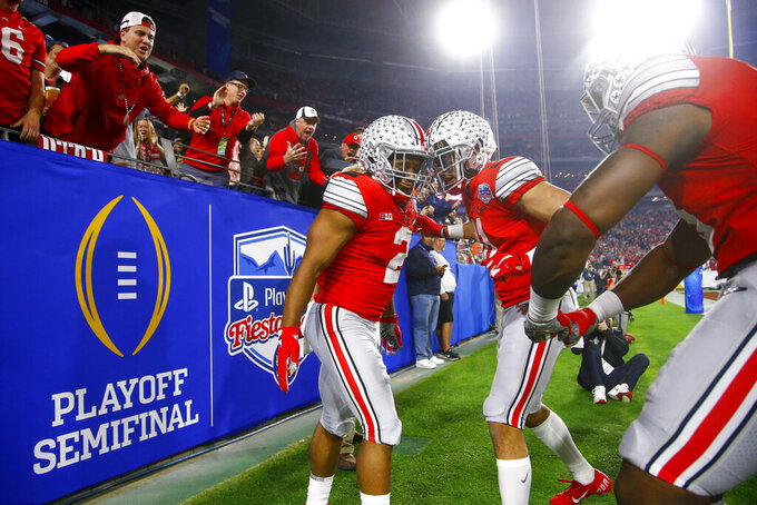 FILE - In this Dec. 28, 2019, file photo, Ohio State running back J.K. Dobbins, left, celebrates his touchdown with wide receiver Austin Mack during the first half of the team's Fiesta Bowl NCAA college football playoff semifinal against Clemson,  in Glendale, Ariz. Clemson is preseason No. 1 in The Associated Press Top 25, Monday, Aug. 24, 2020, a poll featuring nine Big Ten and Pac-12 teams that gives a glimpse at what's already been taken from an uncertain college football fall by the pandemic. Ohio State was a close No. 2. (AP Photo/Ross D. Franklin, File)