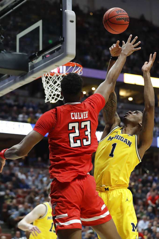 Texas Tech guard Jarrett Culver, left, shoots over Michigan guard Charles Matthews during the second half an NCAA men's college basketball tournament West Region semifinal Thursday, March 28, 2019, in Anaheim, Calif. (AP Photo/Marcio Jose Sanchez)