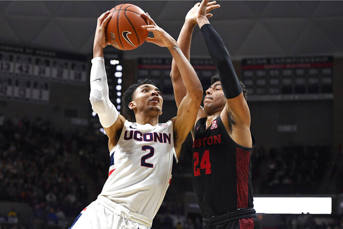 Connecticut's James Bouknight (2) shoots as Houston's Quentin Grimes (24) defends in the first half of an NCAA college basketball game, Thursday, March 5, 2020, in Storrs, Conn. (AP Photo/Jessica Hill)