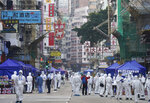 Government investigators wearing protective suits gather in the Yau Ma Tei area in Hong Kong, Saturday, Jan. 23, 2021. Thousands of Hong Kong residents were locked down Saturday in an unprecedented move to contain a worsening outbreak in the city, authorities said. (AP Photo/Vincent Yu)