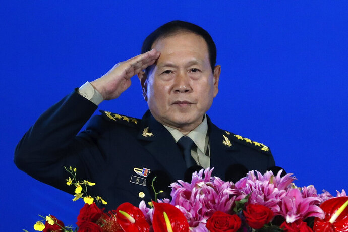 In this Monday, Oct. 21, 2019, photo, Chinese Defense Minister Wei Fenghe salutes after delivering his opening speech for the Xiangshan Forum, a gathering of the region's security officials, in Beijing. China says Wei defended his country's policy on the controversial issues of Hong Kong and the northwestern territory of Xinjiang in a telephone conversation with his U.S. counterpart. The official Xinhua News Agency says Wei also raised the issues of Taiwan and the South China Sea in the conversation on Tuesday, Nov. 5, 2019. (AP Photo/Andy Wong)
