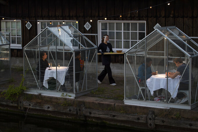 FILE - In this May 5, 2020 file photo, staff at the Mediamatic restaurant serve food to volunteers seated in small glasshouses during a try-out of a setup which respects social distancing abiding by government directives to combat the spread of the COVID-19 coronavirus in Amsterdam, Netherlands. Restaurants around the world try to lure back clientele while keeping them virus-free. (AP Photo/Peter Dejong, File)
