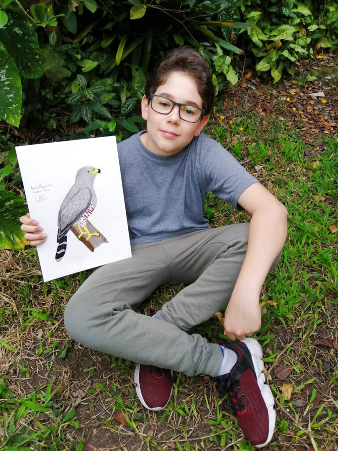In this Aug. 2020 photo provided by Johana Reyes Herrera, Jacobo Rendon, 14, poses with his illustration of an Roadside Hawk in his backyard in El Camino de Viboral, Colombia. Rendon has been working on a photographic and illustrated bird guide that he plans to donate to a local cultural center. (Johana Reyes Herrera via AP)