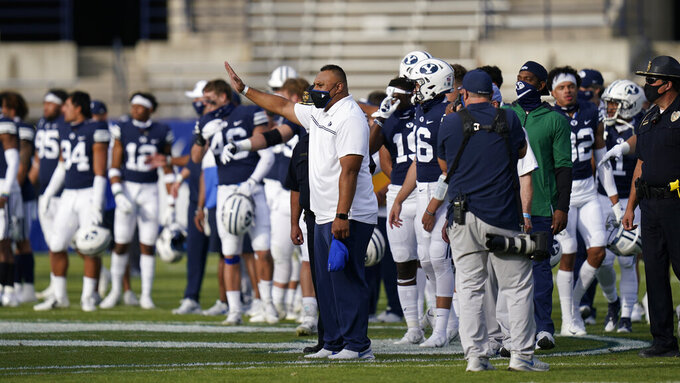 BYU head coach Kalani Sitake, center, walks onto the field following an NCAA college football game against UTSA, Saturday, Oct. 10, 2020, in Provo, Utah. (AP Photo/Rick Bowmer, Pool)