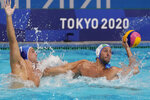 Italy's Gonzalo Echenique, right, is defended by Greece's Georgios Dervisis, left, during a preliminary round men's water polo match at the 2020 Summer Olympics, Tuesday, July 27, 2021, in Tokyo, Japan. (AP Photo/Mark Humphrey)