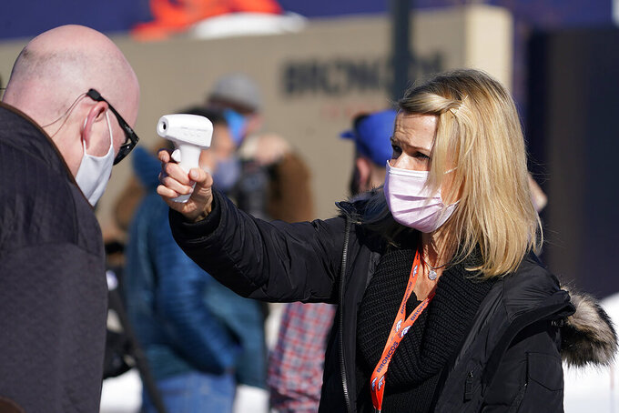 Rachel Deets, right, special events assistant for the Denver Broncos, uses a thermometer to take the temperature of beat writer Ryan O'Halloran before he can watch the team take part in drills during an NFL football practice at the team's headquarters Wednesday, Nov. 25, 2020, in Englewood, Colo. (AP Photo/David Zalubowski)