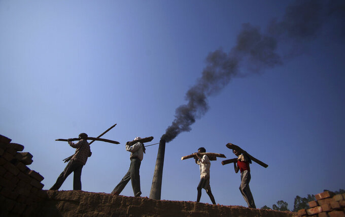 FILE- In this June 4, 2011 file photo, Indian laborers carry firewood, as smoke rises from a bricks factory on the outskirts of Jammu, India. India should commit to carbon neutrality by ending fossil fuel subsidies and investing in clean solar power as it mobilizes trillion of dollars to recover from the coronavirus pandemic, the U.N. Secretary-General António Guterres said Friday, Aug. 28, 2020. (AP Photo/Channi Anand, File)