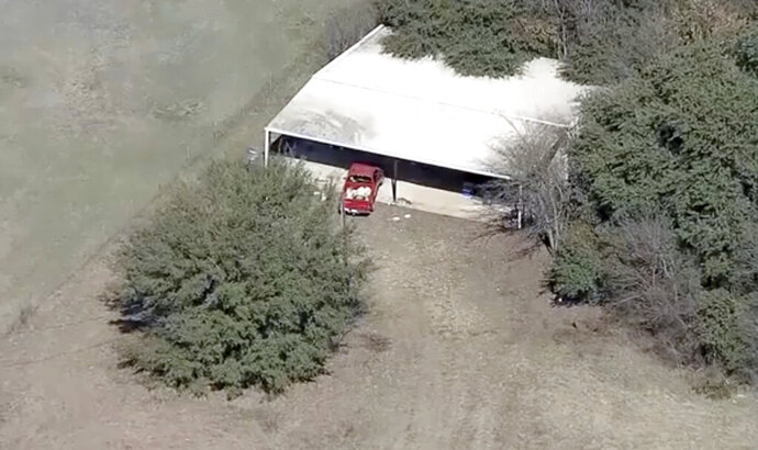 This aerial image provided by KDFW-FOX4 News shows part of the property where deputies found two young, malnourished children locked together in a dog cage near Rhome, Texas about 20 miles (32 kilometers) northwest of Fort Worth. A Texas sheriff says, Tuesday, Feb. 12, 2019, deputies responding to a domestic disturbance at a home discovered two young, malnourished children locked together in a dog cage while two others also were found malnourished. (AP Photo/KDFW-FOX4 News)