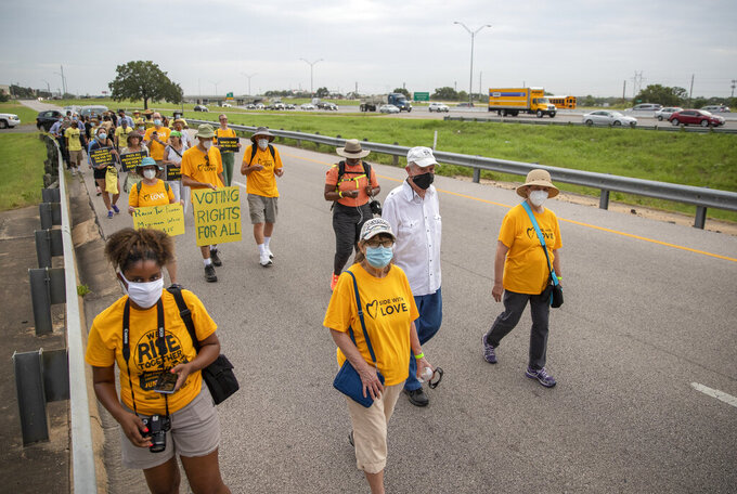 People walk along the service road of Interstate Highway 35, in Georgetown, Texas to participate in a Selma-style march for democracy from Georgetown, Texas to the Texas State Capitol in downtown Austin. On Wednesday, July 28, 2021 the group made a stop at Good Hope church in Round Rock and will end with a rally at the Capitol at 10 am on July 31st. Church leaders and former Democratic congressman Beto O'Rourke are leading a nearly 30-mile voting rights march in Texas.(Ricardo B. Brazziell/Austin American-Statesman via AP)