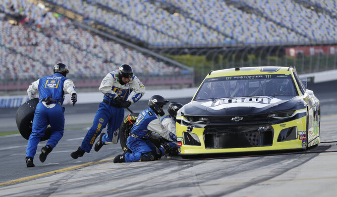 Crew members perform a pit stop on driver Chase Elliott's car during qualifying for Saturday's NASCAR All-Star Cup series auto race at Charlotte Motor Speedway in Concord, N.C., Friday, May 17, 2019. (AP Photo/Chuck Burton)