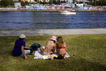 FILE - In this Feb. 5, 2021, file photo, college students study in the sun while people on the other side of the Hillsborough River take part in Super Bowl 55 activities in Tampa, Fla. The city is hosting Sunday's Super Bowl football game between the Tampa Bay Buccaneers and the Kansas City Chiefs. (AP Photo/Charlie Riedel, File)