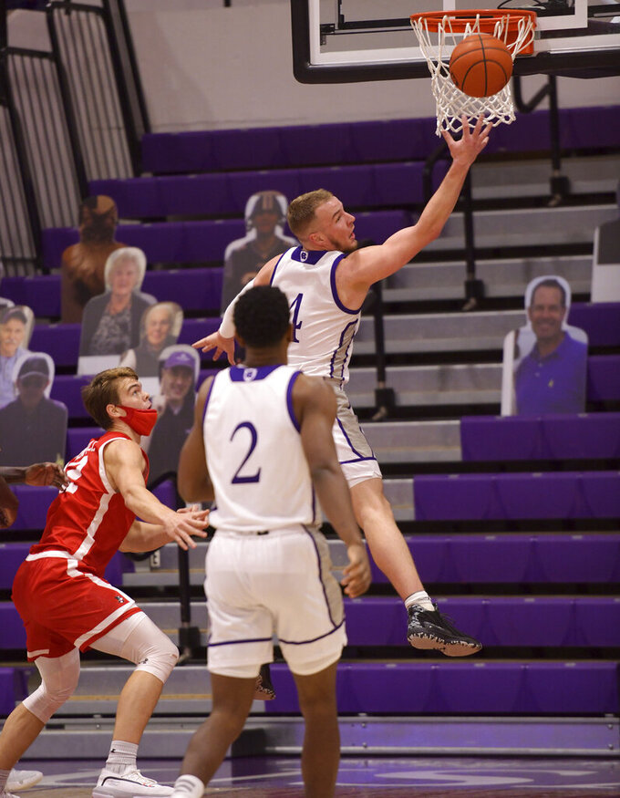 Holy Cross' Austin Butler, top, tosses the ball for two points against Boston during an NCAA college basketball game Monday, Jan. 4, 2021, in Worcester, Mass. (Christine Peterson/Worcester Telegram & Gazette via AP)