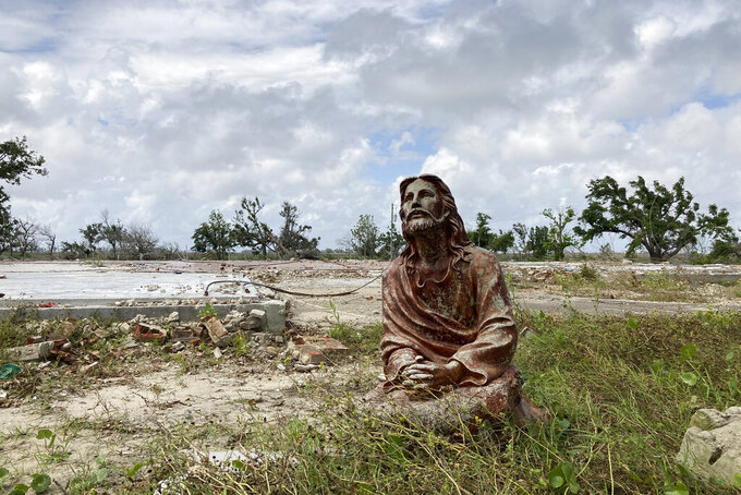 A statue of Jesus Christ stands in front of the remains of a house in Cameron Parish, La. on Monday, May 24, 2021. Scores of people in coastal Louisiana are still living in campers on dirt mounds or next to cement slabs where their houses once stood. Unresolved insurance claims and a shortage of supply and labor are stymying building efforts. And weather forecasters are warning of more possible devastation to come. (AP Photo/Rebecca Santana)