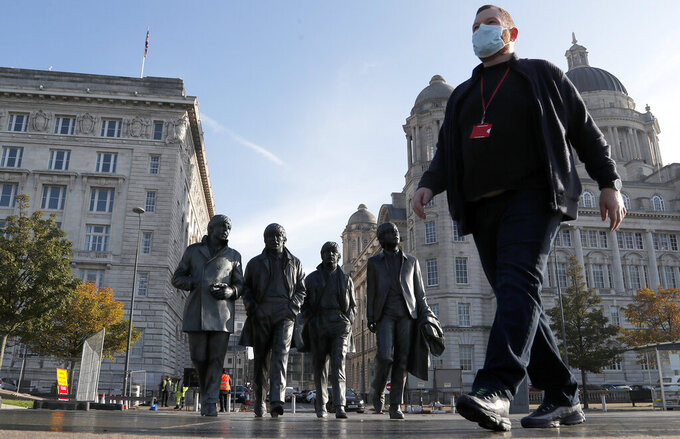 John Ambrose, a guide with the Beatles-themed Fab4 Taxi Tours, wears a face mask as he walks past a statue of the Beatles in Liverpool, England, Wednesday, Oct. 14, 2020. The English port city that gave the world the Beatles weathered decades of industrial decline before becoming a celebrated symbol of urban renewal. Now, the coronavirus is putting Liverpool's hard-won revival in jeopardy, and raising tensions between the north of England and the wealthier south. (AP Photo/Frank Augstein)