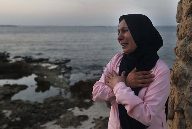 Lebanese Afaf Adulhamid the mother of Mohammed Khaldoun, 27, who is still missing at sea while he was trying with other migrants to reach Cyprus on a boat, cries and prays her son's safe return, as she stands on the coast of Tripoli city, north Lebanon Thursday, Sept. 17, 2020. Mohammed is one of scores of people who have tried in recent weeks to flee Lebanon that is passing through its worst economic and financial crisis in decades to European Union member Cyprus. (AP Photo/Hussein Malla)