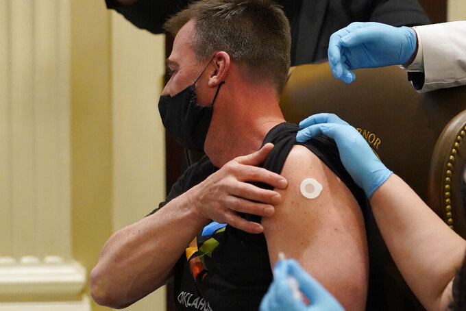 Oklahoma Gov. Kevin Stitt looks away while he is administered the Johnson & Johnson vaccine following a news conference about opening vaccine eligibility, Monday, March 29, 2021, in Oklahoma City. (AP Photo/Sue Ogrocki)