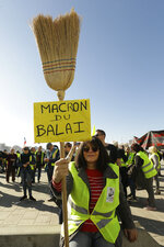 A yellow vest protester holds a broom with a placard reading