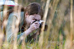 Olivia Chaffin makes photographs in a wooded area as she works on a Girl Scout photography merit badge in Jonesborough, Tenn., on Sunday, Nov. 1, 2020. (AP Photo/Mark Humphrey)