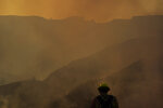 A firefighter pauses for a moment as smoke from the Blue Ridge Fire rises near California 71 on Tuesday, Oct. 27, 2020, in Chino Hills, Calif. Crews tried to beat back two out-of-control wildfires in Southern California that have kept tens of thousands of people out of their homes even as another round of dangerous fire weather raises the risk for flames erupting across the state. (AP Photo/Jae C. Hong)