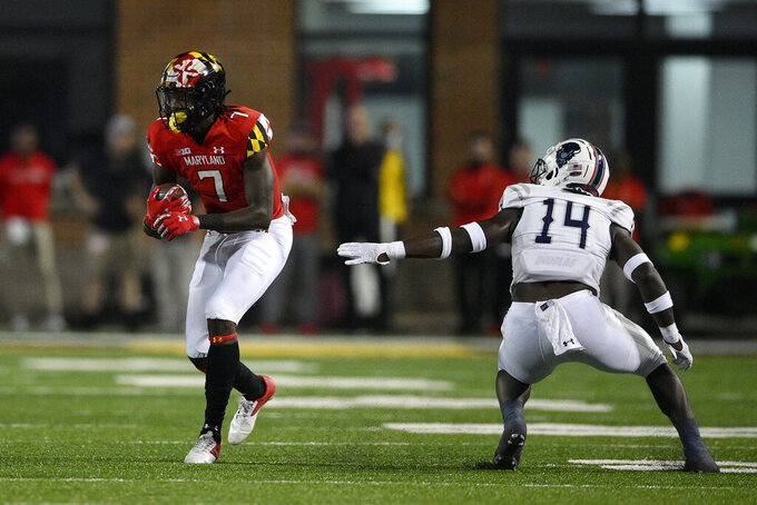 Maryland wide receiver Dontay Demus Jr. (7) carries the ball past Howard defensive back Kenny Gallop (14) during the first half of an NCAA college football game, Saturday, Sept. 11, 2021, in College Park, Md. (AP Photo/Nick Wass)