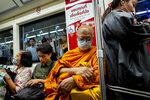 Commuters, including a Buddhist monk wear face masks to protect themselves from new virus in Bangkok, Thailand, Thursday, Feb. 13, 2020. China on Thursday reported over 250 new daily deaths and a spike in daily virus cases of over 15,000 after new methodology was applied in the hardest-hit province of Hubei as to how cases are categorized. (AP Photo/Gemunu Amarasinghe)