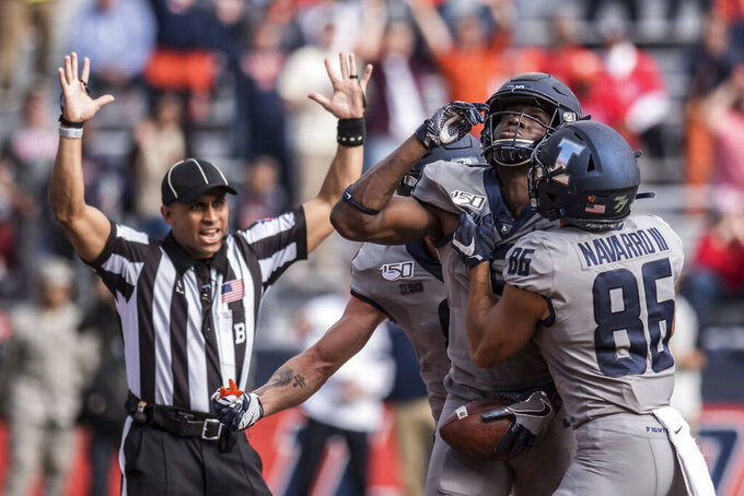 Illinois' Josh Imatorbhebhe, second from right, celebrates with teammates including Donny Navarro (86) after scoring a touchdown in the second half of an NCAA college football game against Wisconsin, Saturday, Oct.19, 2019, in Champaign, Ill. Illinois won 24-21. (AP Photo/Holly Hart)
