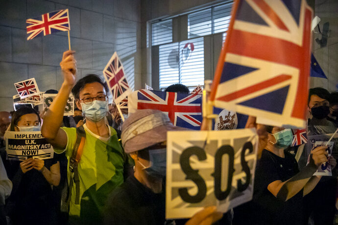 FILE - In this Oct. 23, 2019, file photo, demonstrators wave British flags during a rally outside the British Consulate in Hong Kong. From Tokyo to Brussels, political leaders have swiftly decried Beijing's move to impose a tough national security law on Hong Kong that cracks down on subversive activity and protest in the semi-autonomous territory. But the rhetoric from democratic nations has more bark than bite. (AP Photo/Mark Schiefelbein, File)