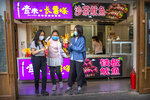 People wearing face masks to protect against the spread of the new coronavirus buy snacks at a shop on a pedestrian shopping street in Beijing, Saturday, May 16, 2020. According to official data released on Saturday India's confirmed coronavirus cases have surpassed China's. (AP Photo/Mark Schiefelbein)
