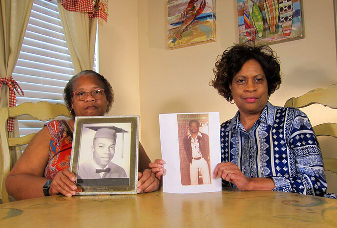In this Wednesday, April 10, 2019, photo Mylinda Byrd Washington, 66, right, and Louvon Byrd Harris, 61, hold up photographs of their brother James Byrd Jr. in Houston. James Byrd Jr. was the victim of what is considered to be one of the most gruesome hate crime murders in recent Texas history. (AP Photo/Juan Lozano)