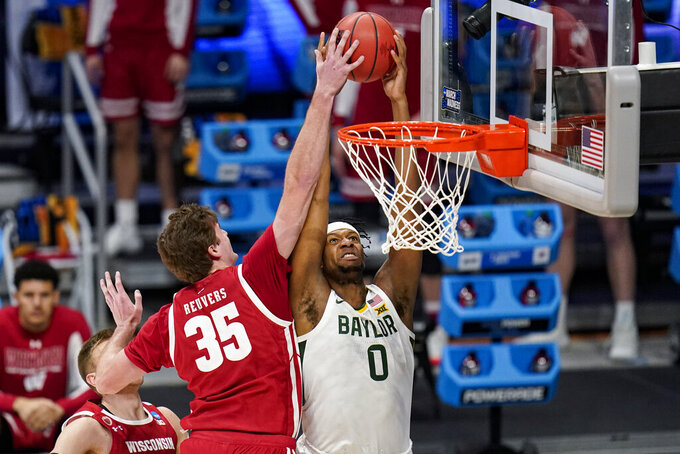 Wisconsin forward Nate Reuvers (35) blocks the dunk attempt of Baylor forward Flo Thamba (0) in the first half of a second-round game in the NCAA men's college basketball tournament at Hinkle Fieldhouse in Indianapolis, Sunday, March 21, 2021. (AP Photo/Michael Conroy)