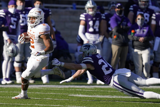 Texas running back Roschon Johnson (2) gets past Kansas State defensive back Brock Monty (24) during the second half of an NCAA college football game in Manhattan, Kan., Saturday, Dec. 5, 2020.  (AP Photo/Orlin Wagner)